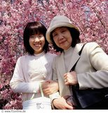 Asian women standing in front of cherry blossom