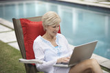 Frau mit Laptop am Pool