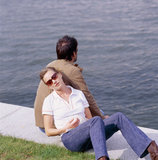 Young couple sitting on the edge of a river