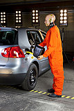 Ein Crashtest dummy putting Gas in einem Auto