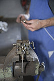 Germany, Ebenhausen, Mechatronic technician working on machine part in car garage, close up