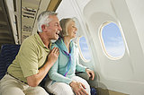Germany, Munich, Bavaria, Senior couple looking out through window in economy class airliner