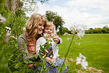 Mother and daughter sitting in field with wildflowers