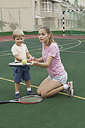 A mother teaching her son how to balance a tennis ball on a racket