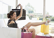 Excited woman in living room with shopping bags