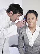Germany, Hamburg, Doctor examining patient ear with medical equipment