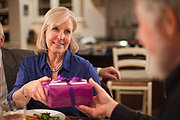 Mature woman at dinner party receiving gift