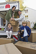 Germany, Bavaria, Grobenzell, Family with cardboard boxes for moving house, smiling, portrait