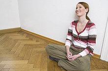 Frau sitzen auf Boden und Musikhören mit Kopfhörern