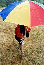Ein Junge mit einem Regenschirm ausgeführt.