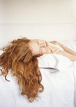 Rothaarige Frau auf dem Bett liegend