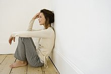 Eine junge Frau sitzt in der Ecke von einem leeren Raum