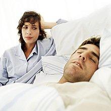 Porträt eines jungen Mannes schlafen während seiner Frau starrt ihn an