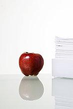 Einen Apfel und ein Haufen Papiere.