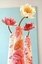 Einzelne Seerosen in Vasen im Frottee-Design