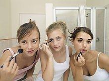 Drei Mädchen im Teenageralter (15-17) Anwendung Make-up im Badezimmer
