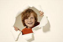 Porträt von Boy suchen durch Papier Loch