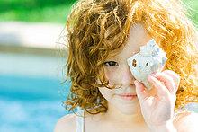 Little Mädchen hält Seashell Gesicht, Blick in die Kamera