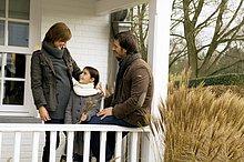 Mädchen stehen und lächelnd mit ihren Eltern in einem Balkon