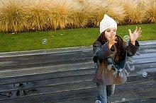 Mädchen steht auf einer Promenade und fangen Blasen