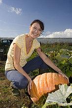 Frau mit Kürbis im Garten, lächelnd, portrait