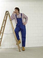 Mann in Arbeitskleidung neben einer Leiter