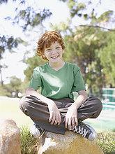 Junge sitzt im park