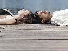 Ein junges paar auf einer Mole Kopf an Kopf liegend
