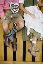 Paar in Tracht sitzt auf Holzgeländer, Mann mit Lebkuchenherz, Oktoberfest