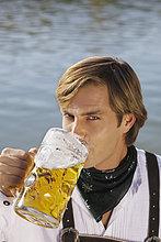 Junger Mann in Tracht trinkt Mass Bier, Biergarten am Seehaus, Englischer Garten, Nahaufnahme