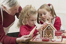 Kleine Mädchen verzieren mit Grossmutter Lebkuchenhaus