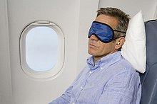 Ein Mann mit einer Schlafmaske schlafen auf einer Ebene