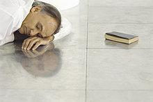 älterer Mann liegt auf gefliesten Boden ruhelosigkeit Kopf auf Arm, schlafen, geschlossenes Buch liegen in der Nähe