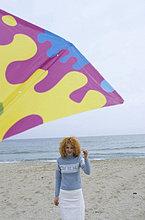 Junge Frau mit roten Locken hält einen Drachen an einer Schnur - Freizeit - Spaß - Strand - Jahreszeit