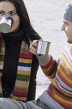 Junges Paar stößt trinkt aus metallischen Bechern - Heißgetränk - Jahreszeit - Strand