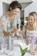 Frau anordnen einer Tabelle für eine Party mit ihrer Tochter
