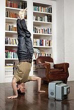 Man standing on Kopf mit tv
