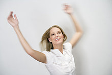 Junge blonde Frau mit weißer Bluse hebt Arme in die Höhe