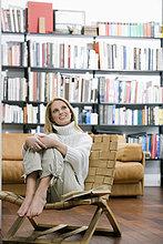 Junge Frau sitzt in Sessel, hohe Bücherregale im Hintergrund