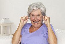 Jubelnde Seniorin mit geballten Fäusten