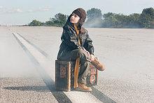 Junge sitzt auf Koffer auf Start-und Landebahn