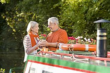Paar hält Flowerpot auf Boot im Kanal
