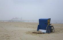 Europa, Deutschland, Mecklenburg-Vorpommern, Usedom, Ahlbeck, Strandkorb am Strand vor der Seebrücke im Nebel