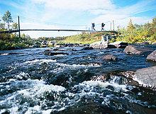 Zwei Männer auf eine Bergtour, überqueren eine Brücke, Schweden.