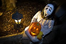 Person in Halloween-Kostüm Kürbis hält