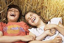 Lachendes Mädchen und Junge liegen in Weizenfeld