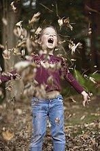 Mädchen wirft Herbstlaub in die Luft