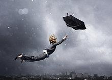 Frau wird von einem Regenschirm weggeblasen