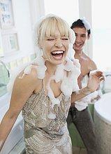 Ausgelassenes Paar im Badezimmer spielt mit Seifenschaum