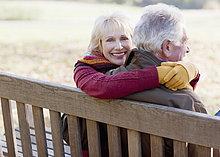 Seniorenpaar umarmt sich auf einer Parkbank